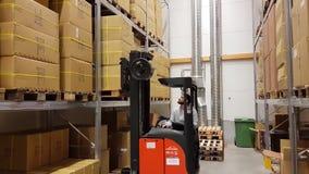 一名有叉架起货车的工人移动的纸盒在仓库/商店里 行业 运输概念, 影视素材
