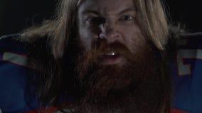 一名有胡子的美式足球在运动器材呼喊的看的球员和胡子的接近的画象有长发的  股票录像