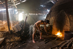 一名木炭工作者在堆的工作慢灼烧的木charcoa 免版税库存照片