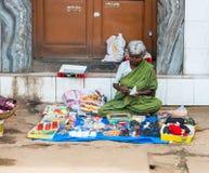 一名未认出的印地安妇女卖男子服饰用品坐p 免版税库存照片