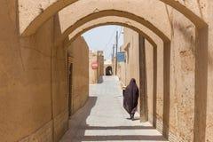 一名未认出的妇女步行沿着向下亚兹德狭窄的街道  免版税库存图片