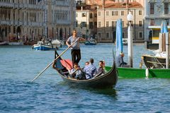 一名梦想的平底船的船夫驾驶有游人的一艘长平底船,威尼斯 意大利 免版税库存图片