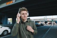 一名正面学生将听到在耳机的音乐,当等待公共交通工具在公共汽车站在桥梁下时 生活方式 免版税库存照片
