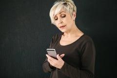 一名正面现代年长妇女拿着一个手机和使用它 更旧的一代和现代技术 库存图片