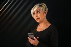 一名正面现代年长妇女拿着一个手机和使用它 更旧的一代和现代技术 免版税库存图片