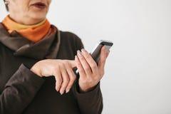 一名正面现代年长妇女拿着一个手机和使用它 更旧的一代和现代技术 免版税图库摄影
