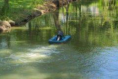 一名浮动水搬家工人,避免死水和蚊子饲养,在一个豪华的泰国庭院公园的周围的水路 免版税库存图片