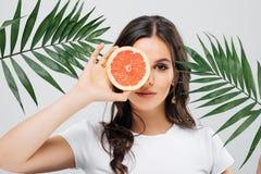一名激动的妇女的画象有摆在与绿色叶子和拿着切的葡萄柚的深色的头发的被隔绝在白色backgro 免版税库存图片