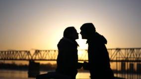 一名爱恋的夫妇、愉快的男人和妇女在铁路桥和日落的背景亲吻 免版税库存照片