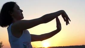 一名爽快亭亭玉立的妇女做挥动的运动用她的手在日落在Slo Mo 股票视频
