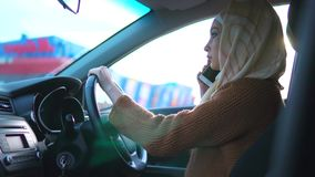 一名现代阿拉伯妇女在电话谈话,驾驶在右手驱动 股票视频