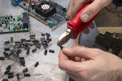 一名电子服务工作者削减电容器的技巧有的钳子 库存照片