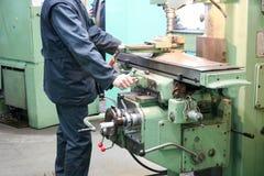 一名男性工作者在一台更大的金属铁锁匠车床,修理的设备,金属工作工作在冶金的一个车间 免版税库存照片