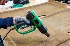 一名男性工作者在他的手上拿着在一个防护手套穿戴的一台绿色工业烘干机并且烘干表面上的胶浆  免版税库存图片