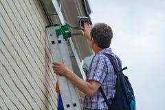 一名男性工作者通过检查和清洗室外安全监视完成维护 免版税图库摄影