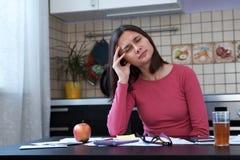 一名疲乏的美丽的妇女的画象坐在厨房里和拿着她的头的一件桃红色夹克的在重音下 库存照片