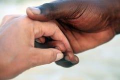 一名白种人妇女和一个非洲人的手 库存图片