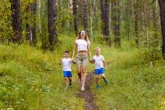 一名白种人苗条微笑的妇女和两个快乐的学龄前儿童孩子沿道路跑的白色T恤的,握手  免版税库存照片