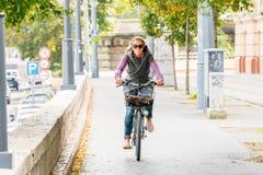 一名白种人骑一辆自行车的妇女佩带的太阳镜的正面图在布达佩斯匈牙利 库存照片