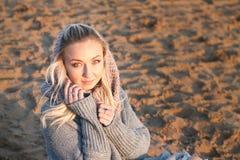 一名白肤金发的卷曲妇女的特写镜头画象坐海滩在日落 库存照片