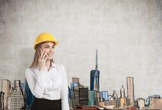 一名白肤金发的女实业家的画象戴一顶黄色安全帽和谈话在她的智能手机 库存图片