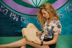 一名白肤金发的妇女在长沙发读一本书 免版税图库摄影