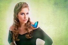 一名白肤金发的妇女的春天概念有一只蓝色蝴蝶的在她嘘 图库摄影