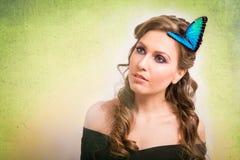 一名白肤金发的妇女的春天概念有一只蓝色蝴蝶的在她的ha 免版税库存照片