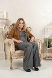 一名白肤金发的妇女的画象绒面革夹克的在壁炉附近的一把椅子 库存图片