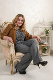 一名白肤金发的妇女的画象绒面革夹克的在壁炉附近的一把椅子 免版税库存图片