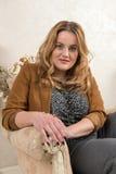 一名白肤金发的妇女的画象绒面革夹克的在壁炉附近的一把椅子 免版税库存照片