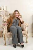 一名白肤金发的妇女的画象绒面革夹克的在壁炉附近的一把椅子 库存照片