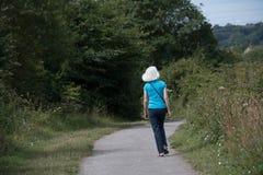 一名白肤金发的妇女走乡下道路 免版税库存照片