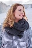 一名白肤金发的胖的妇女的画象冬天夹克和厚实的围巾的 免版税库存照片