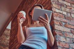 一名白肤金发的行家妇女的画象在有a的时一间屋子里拿着一杯咖啡,当看某事在一种数字式片剂 免版税库存图片