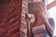 一名白肤金发的行家妇女的画象在有a的时一间屋子里拿着一杯咖啡,当看某事在一种数字式片剂 免版税图库摄影