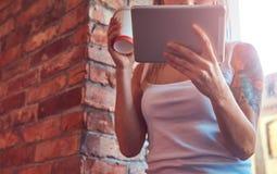 一名白肤金发的行家妇女的画象在有a的时一间屋子里拿着一杯咖啡,当看某事在一种数字式片剂 库存图片