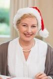 一名相当成熟妇女的画象圣诞老人帽子的 库存照片
