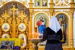 一名祈祷的妇女在一个正统基督教会里在圣洁手,克拉斯诺达尔疆土村庄  免版税库存照片