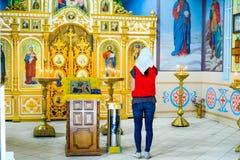 一名祈祷的妇女在一个正统基督教会里在圣洁手,克拉斯诺达尔疆土村庄  免版税图库摄影