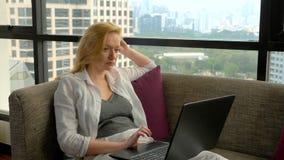 一名端庄的妇女在沙发说谎由俯视摩天大楼和使用她的膝上型计算机的全景窗口 影视素材