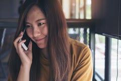 一名美丽的亚裔妇女举行和谈话在巧妙的电话 免版税库存照片