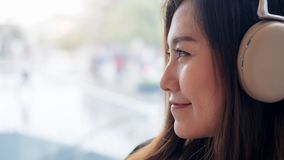 一名美丽的亚裔妇女喜欢听到与耳机的音乐在充满感觉的现代咖啡馆放松和愉快 库存照片