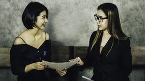 一名美丽的亚裔妇女坐一把木椅子,当为与公司的人力资源委员会,概念的一次采访时 库存照片