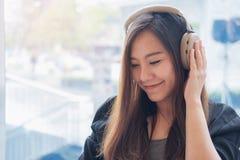 一名美丽的亚裔妇女的特写镜头图象喜欢听到与耳机的音乐在充满感觉的现代咖啡馆放松 免版税图库摄影