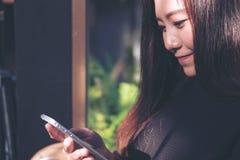 一名美丽的亚裔妇女的特写镜头图象有兴高采烈的面孔的使用和看巧妙的电话 免版税图库摄影