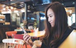 一名美丽的亚裔妇女的特写镜头图象有兴高采烈的面孔的使用和看巧妙的电话 免版税库存图片