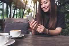 一名美丽的亚裔妇女的特写镜头图象有兴高采烈的面孔藏品和使用的巧妙的电话有在木桌上的咖啡杯的 免版税图库摄影