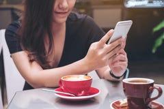 一名美丽的亚裔妇女的特写镜头图象有兴高采烈的面孔藏品和使用的巧妙的电话有在玻璃桌上的咖啡杯的 免版税库存照片