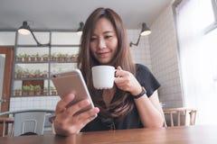一名美丽的亚裔妇女的特写镜头图象有兴高采烈的面孔藏品和使用的巧妙的电话,当喝在木桌上时的热的咖啡 库存照片